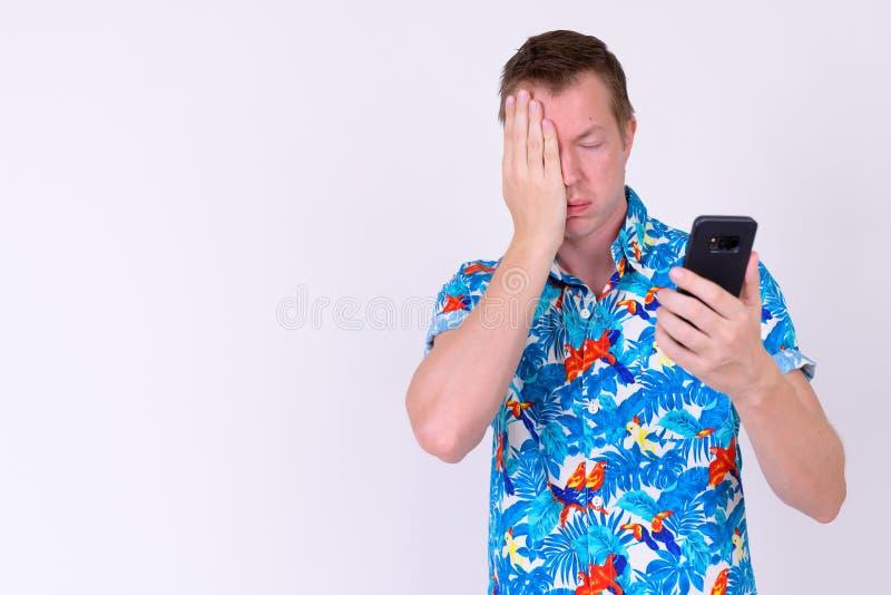 Retrato do homem forçado novo do turista que usa o telefone e obtendo más notícias foto de stock