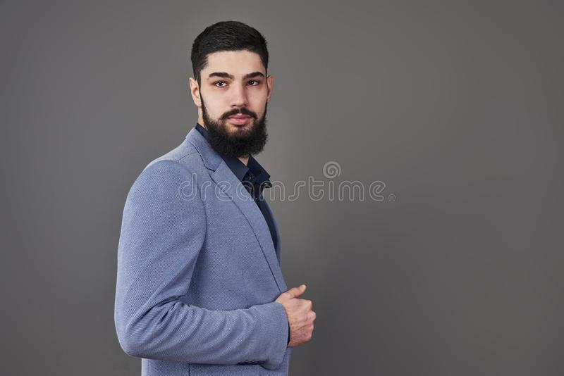 Retrato do homem do freelancer com a barba no revestimento que está contra o contexto cinzento foto de stock