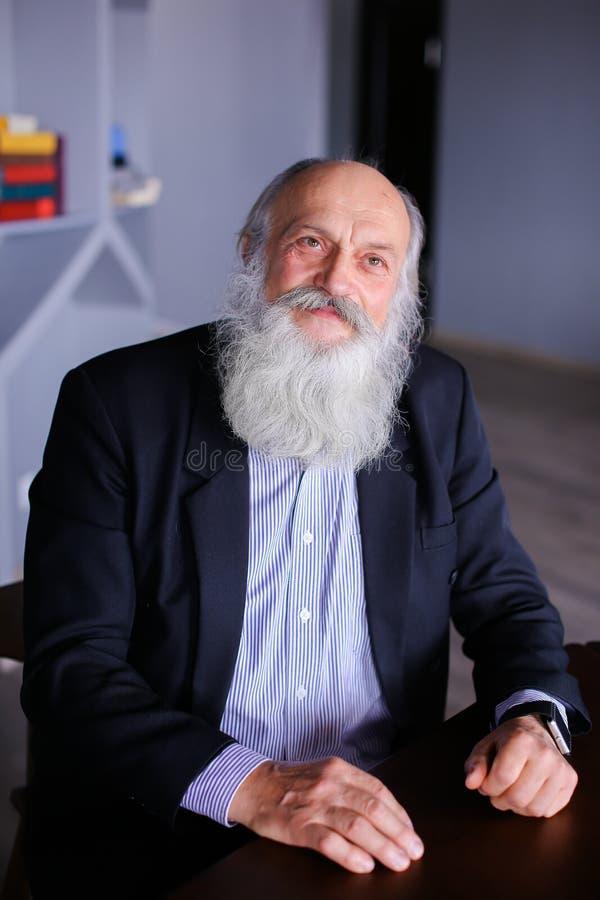 Retrato do homem idoso esperto que reflete na vida e wi do levantamento fotografia de stock royalty free