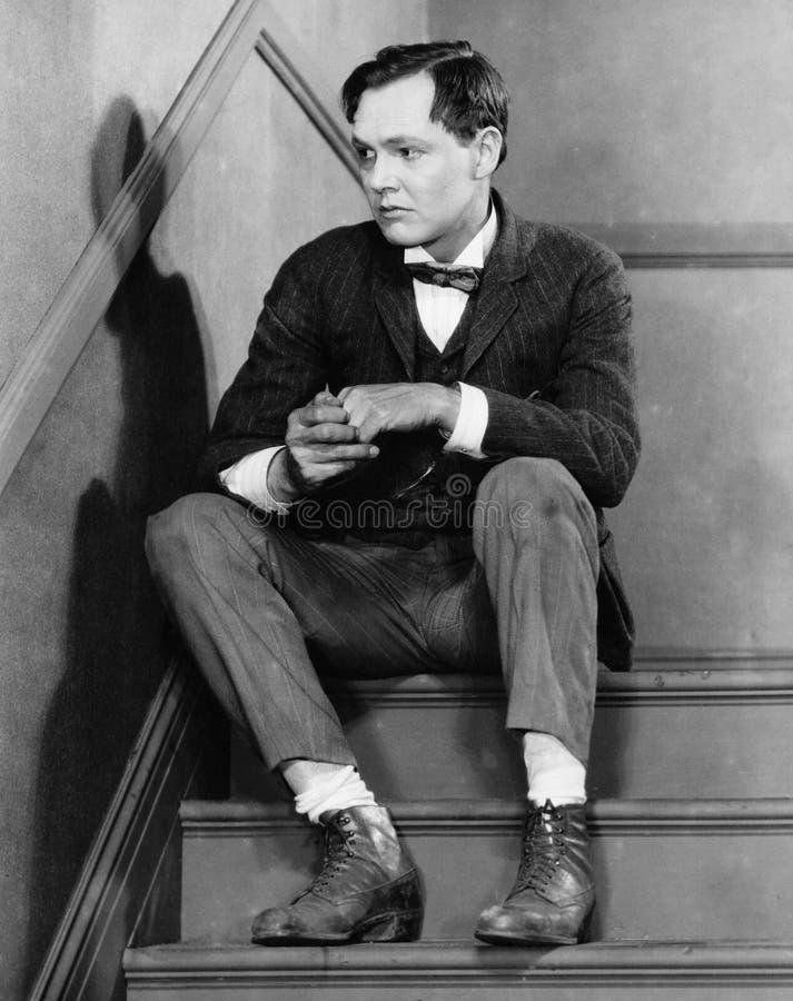 Retrato do homem incomodado que senta-se em escadas (todas as pessoas descritas não são umas vivas mais longo e nenhuma proprieda imagem de stock