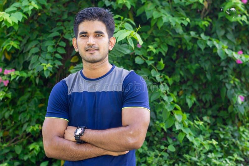 Retrato do homem indiano novo no parque no fundo verde imagem de stock