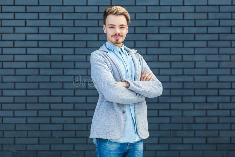 Retrato do homem louro novo considerável bem sucedido feliz no estilo ocasional que está com braços cruzados e que olha a câmera  fotografia de stock