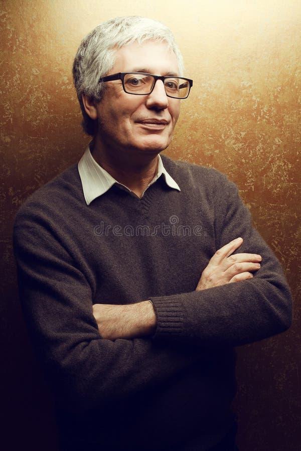 Retrato do homem maduro feliz que está com mãos cruzadas fotografia de stock royalty free