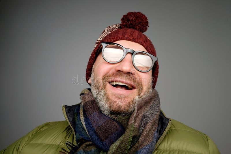 Retrato do homem maduro do moderno nos vidros e no levantamento do chapéu Homem farpado de sorriso que veste a roupa morna para o fotos de stock