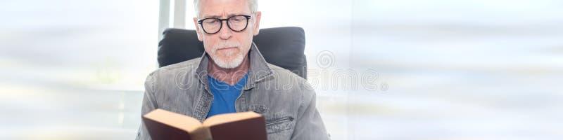 Retrato do homem maduro que lê um livro imagens de stock royalty free