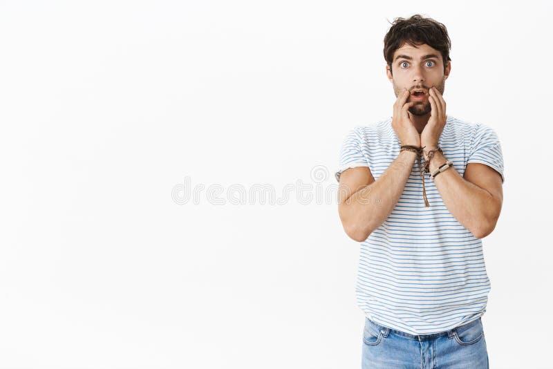 Retrato do homem masculino novo nervoso e chocado shcoked com olhos azuis e a maxila deixando cair do cabelo desarrumado que toca foto de stock royalty free