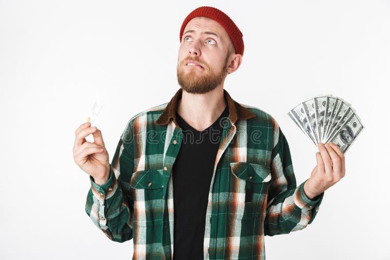 Retrato do homem do moderno que guarda o cartão de crédito e do fã do dinheiro do dólar, ao estar isolado sobre o fundo branco fotos de stock