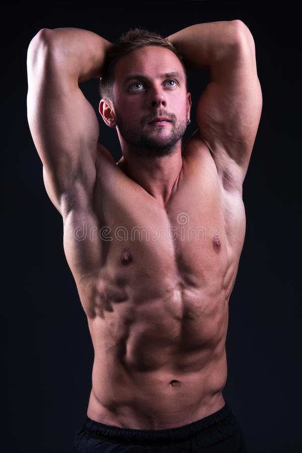 Retrato do homem muscular considerável novo que levanta sobre o cinza foto de stock