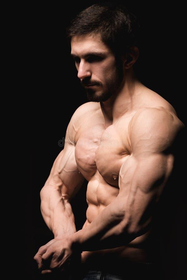Retrato do homem muscular descamisado no calças de brim Pão masculino novo que mostra seus corpo e músculos perfeitos no fundo pr imagem de stock