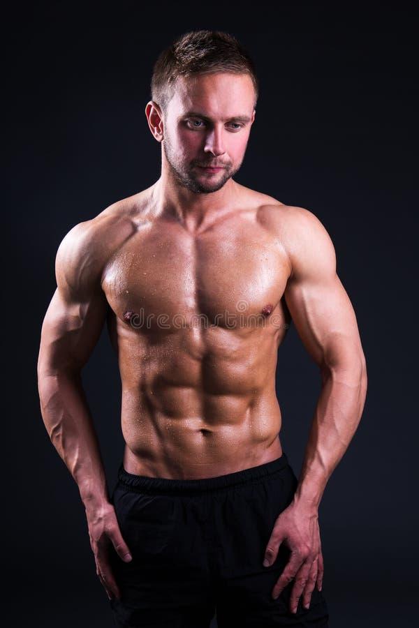 Retrato do homem muscular novo que está sobre o cinza imagens de stock royalty free