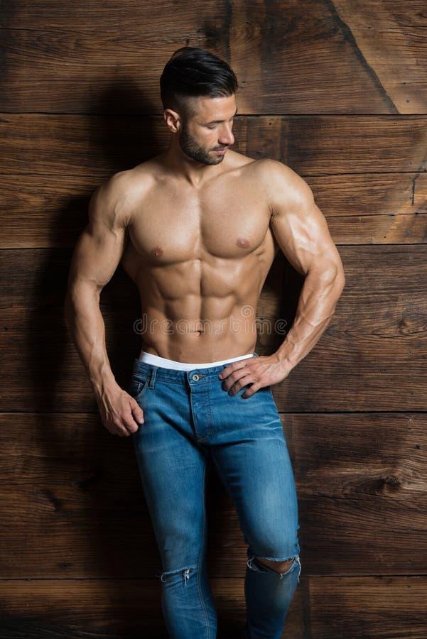 Retrato do homem muscular que está perto da parede imagem de stock