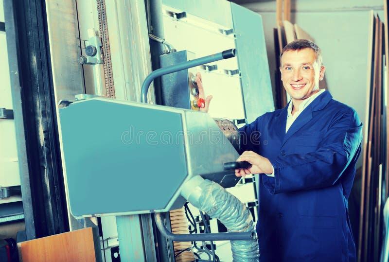 Retrato do homem no uniforme que trabalha no grande machin automático da serra fotografia de stock royalty free