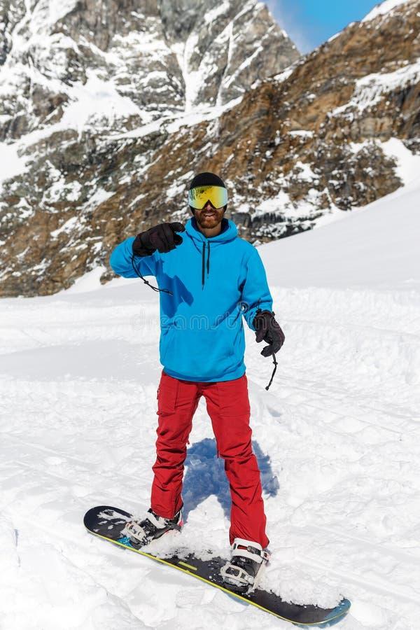 Retrato do homem nos óculos de esqui com reflexo de montanhas nevadas Homem de roupas azuis e óculos de esqui foto de stock