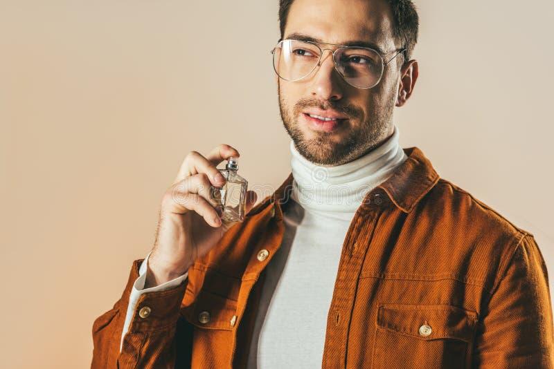 retrato do homem novo à moda que aplica o perfume foto de stock