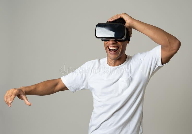 Retrato do homem novo alegre e chocado que veste os auriculares da realidade virtual que exploram o mundo 3D imagem de stock royalty free