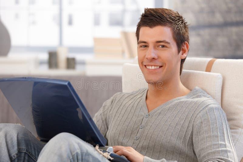 Retrato do homem novo alegre que usa o computador foto de stock