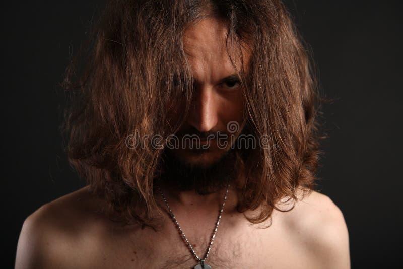 Retrato do homem novo atrás de seu cabelo foto de stock