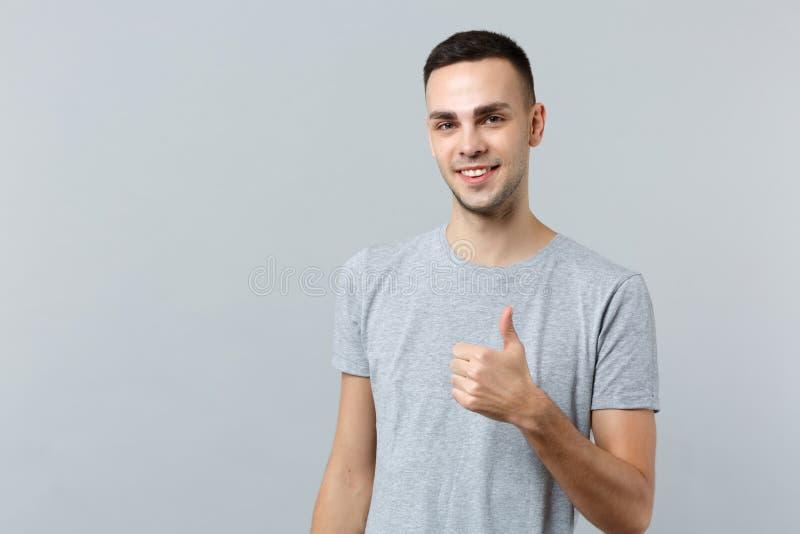 Retrato do homem novo atrativo de sorriso na roupa ocasional que está e que mostra o polegar acima do isolado na parede cinzenta imagens de stock royalty free