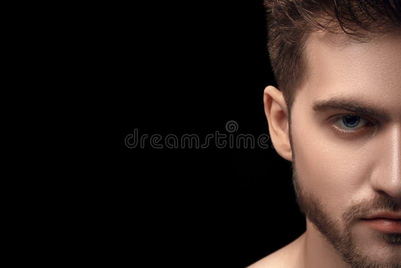 Retrato do homem novo bonito com olhos azuis no fundo preto escuro Meio retrato da cara do homem com barba Metade atrativa do ind imagem de stock