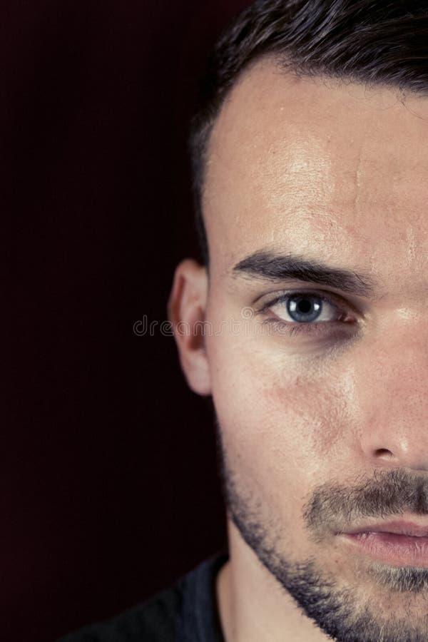 Retrato do homem novo bonito com os olhos verdes no fundo do preto escuro e do vermelho Meio retrato da cara do homem com a maxil fotografia de stock