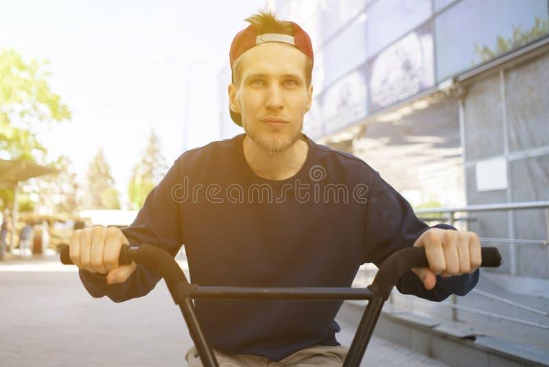 Retrato do homem novo cheereful na bicicleta, montando nas ruas da cidade fotos de stock royalty free
