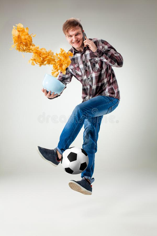 Retrato do homem novo com a bola esperta do telefone e do futebol imagem de stock royalty free