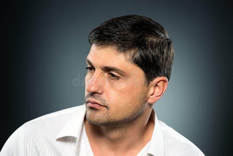 Retrato do homem novo com a cara muito considerável em s ocasional branco imagem de stock royalty free