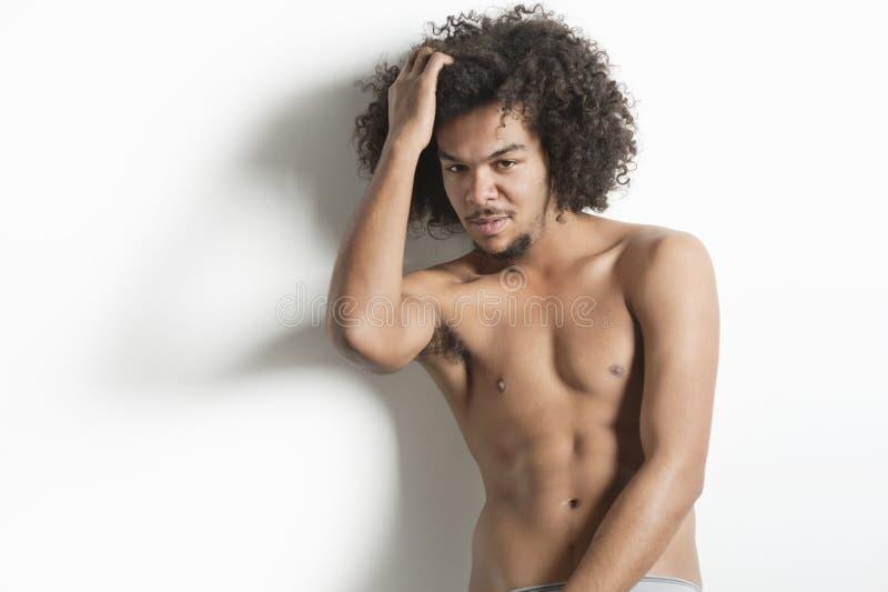 Retrato do homem novo com levantamento com mão no cabelo sobre o fundo branco imagens de stock royalty free