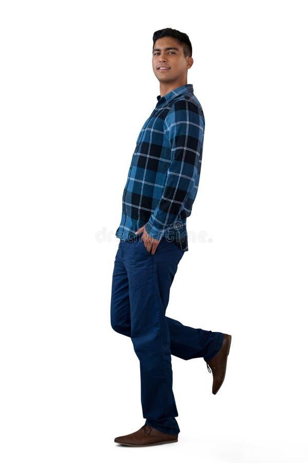 Retrato do homem novo com mãos em uns bolsos que estão em um pé fotos de stock royalty free