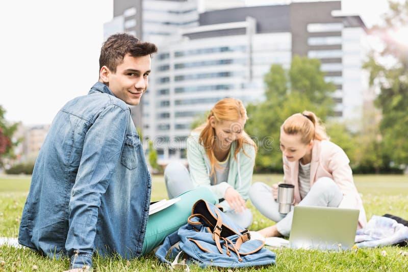 Retrato do homem novo com os amigos fêmeas que estudam no campus universitário foto de stock