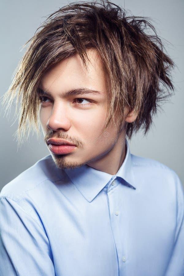Retrato do homem novo com penteado desarrumado da franja Tiro do estúdio imagem de stock royalty free