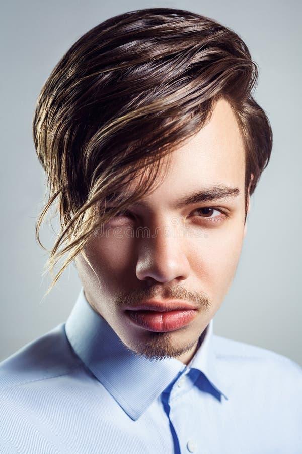 Retrato do homem novo com penteado longo da franja em seus olhos imagens de stock
