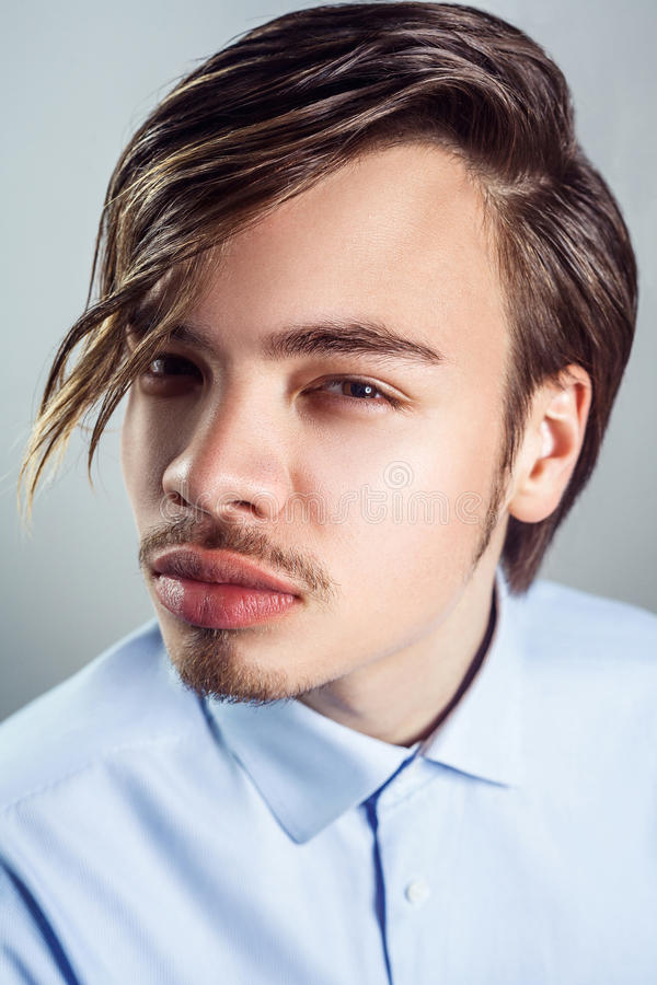 Retrato do homem novo com penteado longo da franja em seus olhos foto de stock royalty free