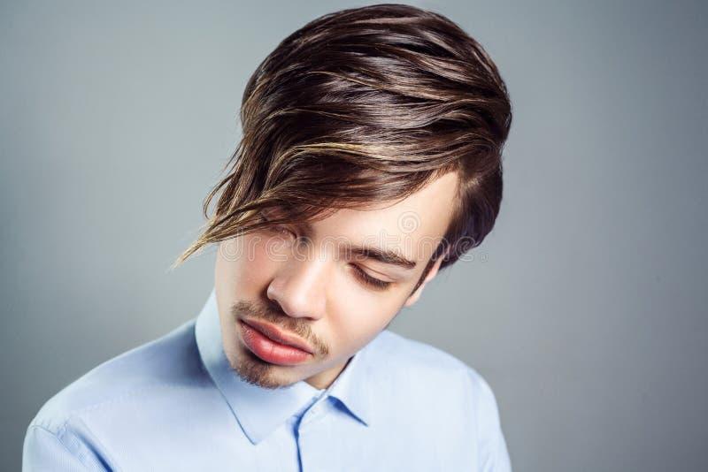 Retrato do homem novo com penteado longo da franja em seus olhos fotografia de stock