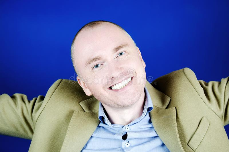 Retrato do homem novo com sorriso neve-branco Cabelo curto, revestimento de creme e um fundo azul Emo??es e sorriso imagem de stock