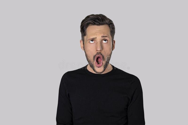 Retrato do homem novo com uma expressão engraçada isolado no fundo cinzento imagens de stock royalty free