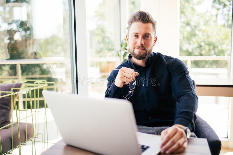 Retrato do homem novo com vidros nas mãos que sentam-se em sua mesa no escritório foto de stock royalty free