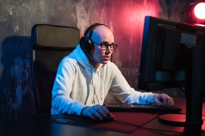 Retrato do homem novo concentrado nos vidros e nos auriculares na sala escura que joga o jogo de computador em linha ou que compe fotos de stock royalty free