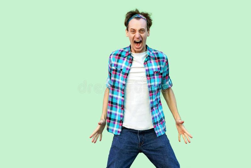 Retrato do homem novo confuso irritado na posição quadriculado azul ocasional da camisa e da faixa, olhando a câmera com cara agr imagem de stock royalty free