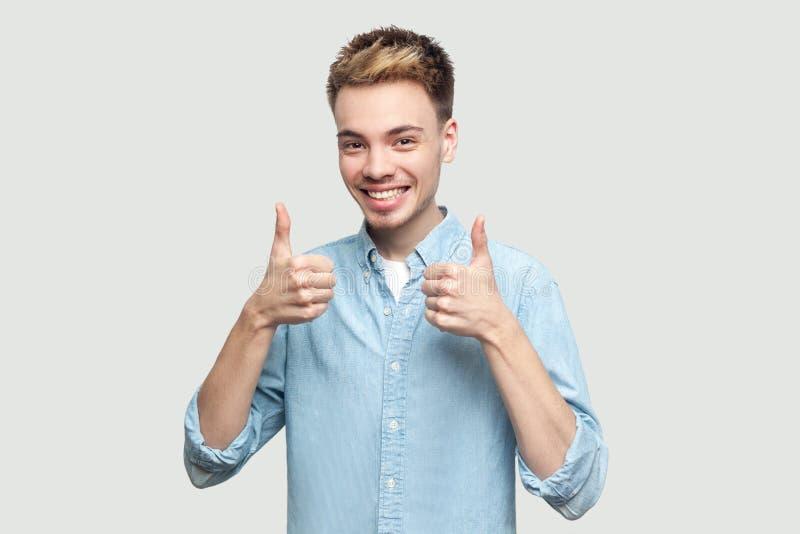 Retrato do homem novo consider?vel bem sucedido satisfeito feliz em claro - posi??o azul da camisa, polegares acima e olhando a c fotografia de stock