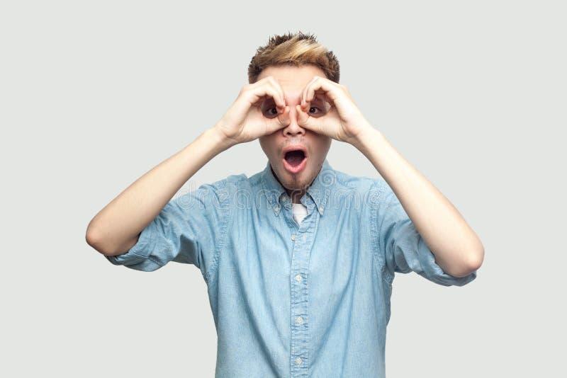 Retrato do homem novo considerável chocado em claro - posição azul da camisa com mãos no gesto dos binóculos dos olhos e vista da fotografia de stock royalty free