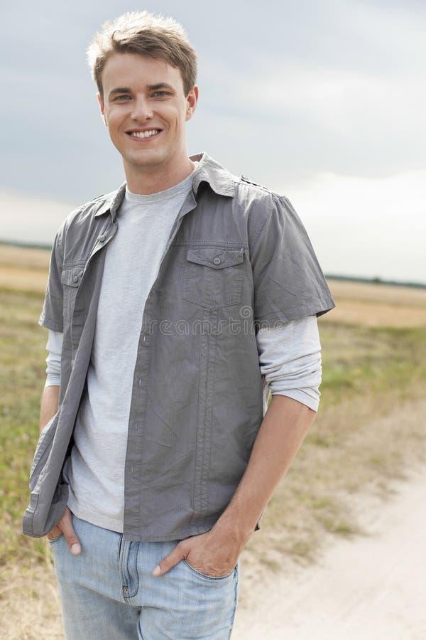 Retrato do homem novo considerável com mãos em uns bolsos que estão no campo imagens de stock