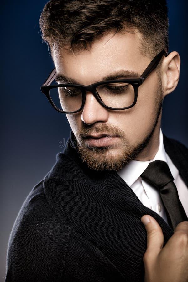 Retrato do homem novo considerável com vidros no fundo azul fotografia de stock royalty free