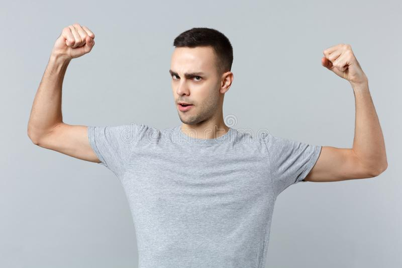 Retrato do homem novo considerável forte na roupa ocasional que espalha as mãos, mostrando o bíceps, músculos isolados no cinza fotos de stock