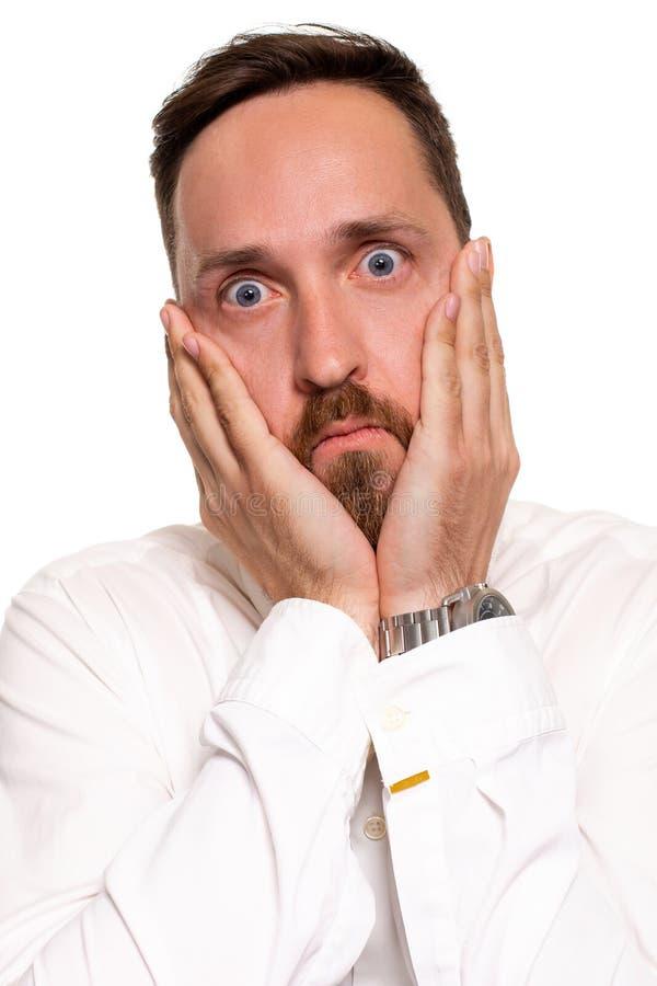 Retrato do homem novo considerável incomodado na camisa branca que guarda as palmas perto do mordente imagem de stock royalty free