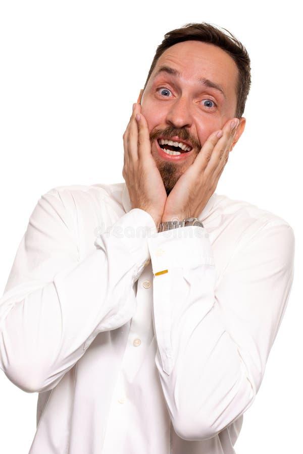 Retrato do homem novo considerável incomodado na camisa branca que guarda as palmas perto do mordente imagens de stock