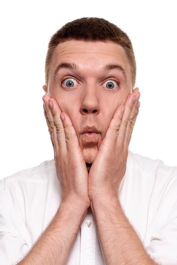 Retrato do homem novo considerável incomodado na camisa branca que guarda as palmas perto do mordente fotografia de stock