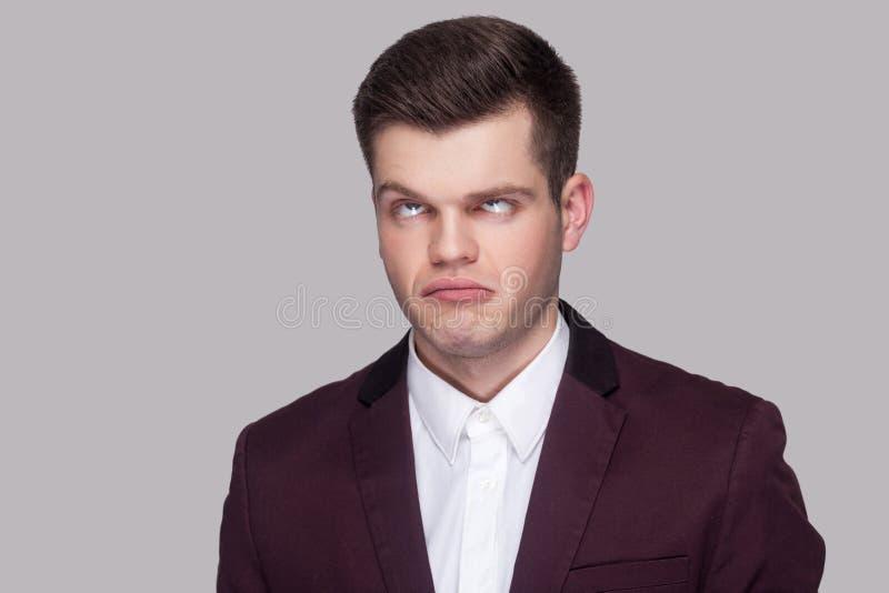 Retrato do homem novo considerável louco engraçado no terno e no wh violetas fotografia de stock royalty free