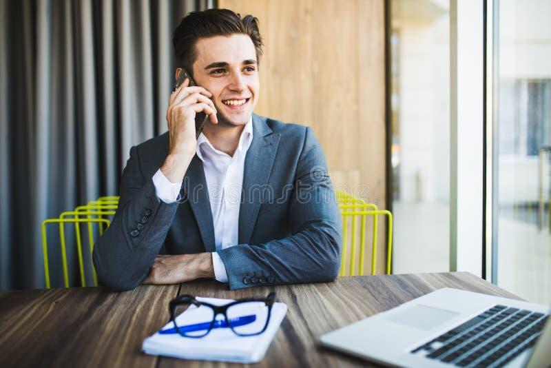 Retrato do homem novo considerável nos vidros que sentam-se na mesa de escritório com laptop e que falam no telefone celular foto de stock royalty free