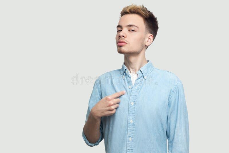 Retrato do homem novo consider?vel orgulhoso em claro - posi??o azul da camisa, apontando-se e olhando a c?mera com cara s?ria foto de stock